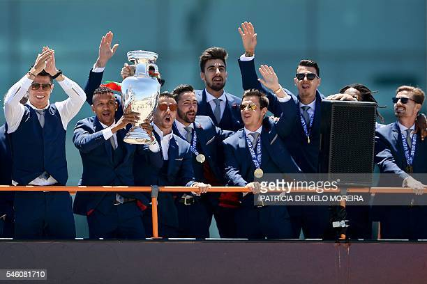 Portugal's national football team members celebrate with the trophy on an open top bus on arrival at Lisbon airport on July 11 2016 after their Euro...