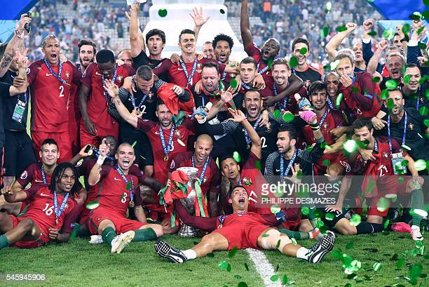 Portugal's players pose with the trophy as they celebrate after beating France during the Euro 2016 final football match at the Stade de France in...
