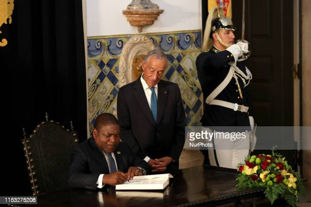 Portugal's President Marcelo Rebelo de Sousa looks to Mozambique's president Filipe Nyusi as he signs the honor book before their meeting at the...