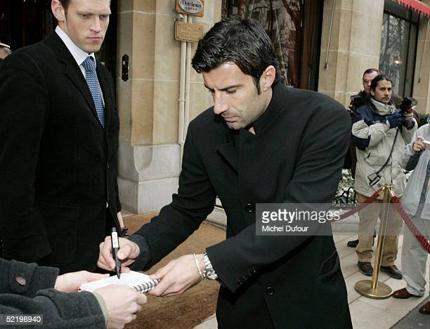 Portugese footballer Luis Figo signs autographs as he leaves his Paris hotel The Plaza to attend Real Madrid teammate Ronaldo's engagement party at...