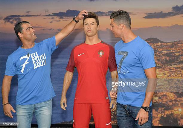Portugese forward Cristiano Ronaldo and his brother Hugo Aveiro pose next to a wax statue representing Ronaldo during a visit to the new location of...