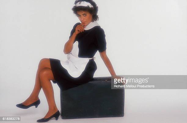 Portuguese actress and writer Linda De Suza sits on a suitcase wearing a French maid's outfit The photograph is a publicity poster for the 1986...