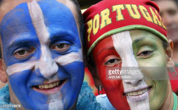 A Portuguese and a Greek fan pose 04 July 2004 at the Luz stadium in Lisbon prior to the Euro 2004 final match between Portugal and Greece at the...