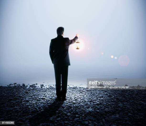 portuguese businessman holding lantern next to water - lantern stock pictures, royalty-free photos & images