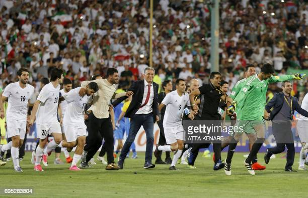 Portuguese coach Carlos Queiroz of the Iranian national football team celebrates among players after winning the 2018 World Cup qualifying football...