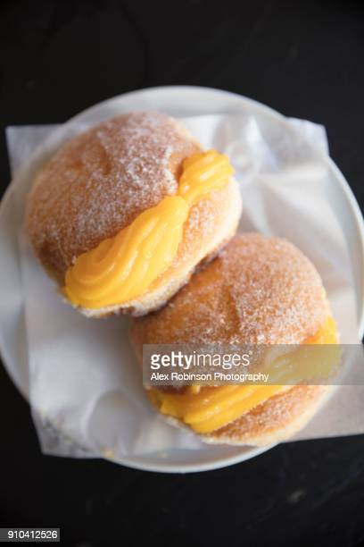 portuguese custard doughnuts on a plate - traditionally portuguese stock pictures, royalty-free photos & images
