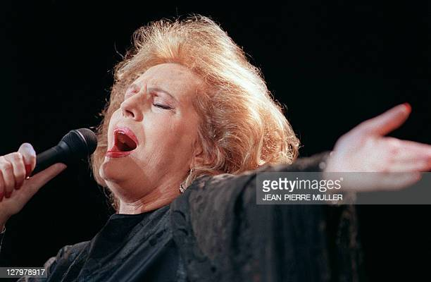 Portuguese fado singer Amalia Rodrigues performs on the stage of the ChampsElysées theatre on March 20 1990 in Paris Rodrigues' speciality was fado...