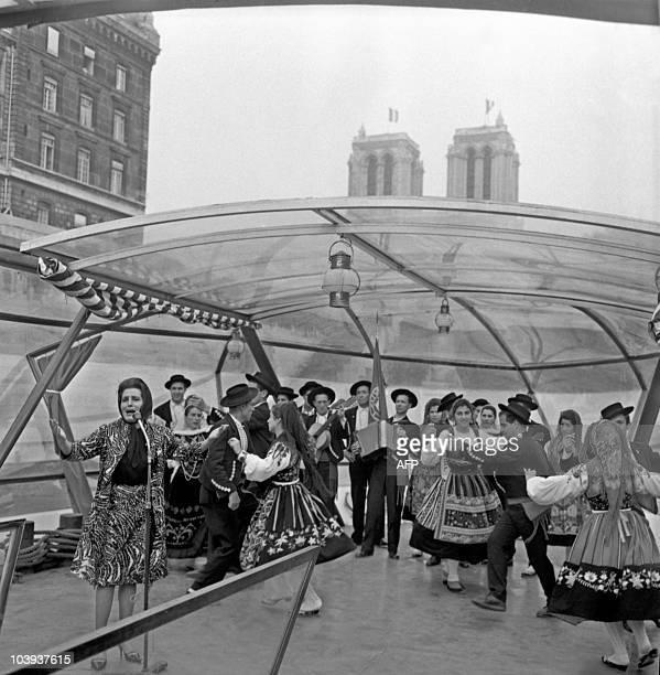 Portuguese fado singer Amalia Rodrigues performs with the folk group Santa Maria de Portuzelo on a Seine pleasure boat on May 28 1963 in Paris...