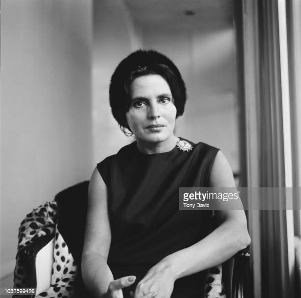 Portuguese fado singer Amalia Rodrigues posed seated in a chair on 15th April 1963