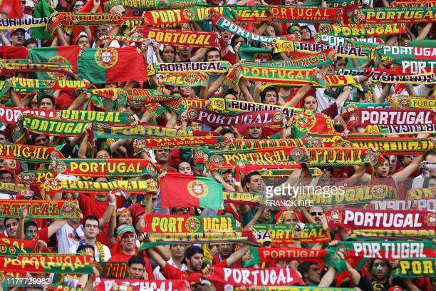 Portuguese fans cheer their team 04 July 2004 at the Luz stadium in Lisbon before the beginning of the Euro 2004 final match between Portugal and...
