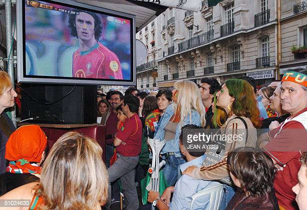 Portuguese fans crowd around a plasma screen at a Paris cafe to watch the Euro2004 football final between Grece and Portugal 04 July 2004