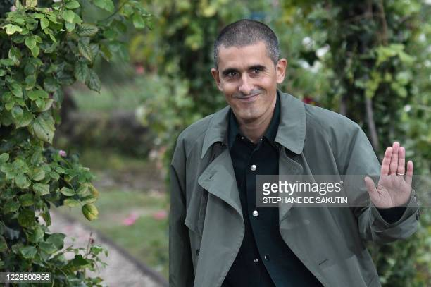 Portuguese fashion designer and artistic director Felipe Oliveira Baptista waves at the end of the show by Kenzo during the Paris Fashion Week's...