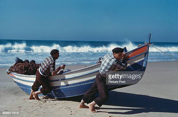 Portuguese fishermen haul their boat up onto the beach at Nazare Portugal 1955 Original Publication Picture Post 7593 Royal Wedding In Portugal unpub