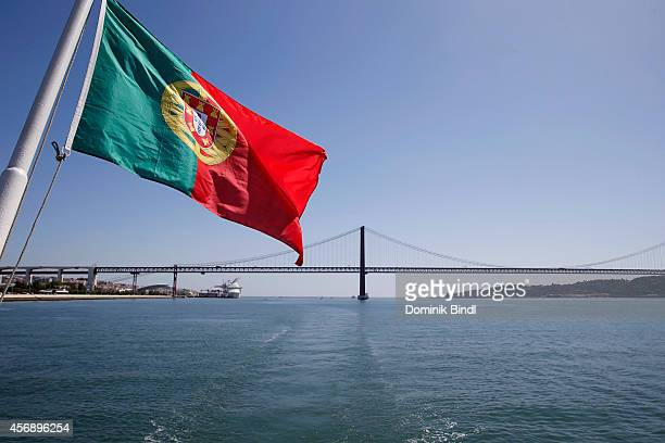 Portuguese Flag waves in sight of the 25 de Abril Bridge between Lisbon and Almada which spans the Tejo River on August 28 2014 in Lisbon Portugal