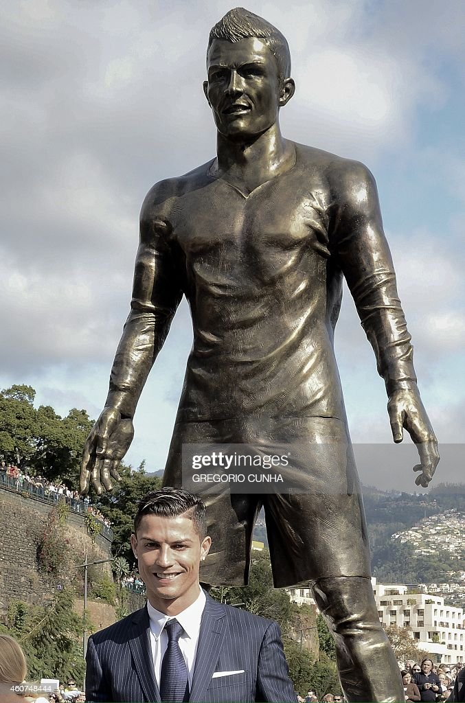 Portuguese football player Cristiano Ronaldo from the Real Madrid poses beneath a statue of himself during the unveling ceremony in his hometown in Funchal on December 21, 2014.