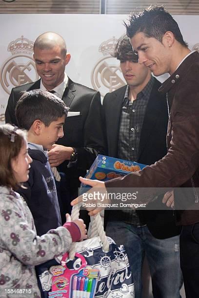Portuguese football player Cristiano Ronaldo hands a toy to a girl next to Real Madrid players Pepe and Kaka during 'En Navidad Ningun Nino Sin...