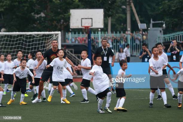 Portuguese footballer Cristiano Ronaldo plays football with students as he visits Beijing Haidian Minzu Primary School during his China tour on July...