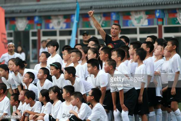 Portuguese footballer Cristiano Ronaldo poses with students as he visits Beijing Haidian Minzu Primary School during his China tour on July 19 2018...