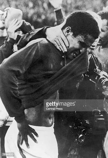 Portuguese footballer Eusebio being led off the pitch in tears after England beat Portugal 21 in a World Cup semifinal at Wembley