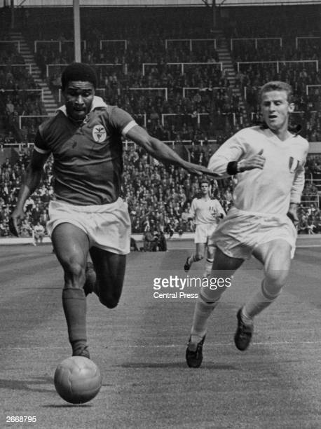 Portuguese footballer Eusebio running past the AC Milan player, Giovanni Trapatoni, during the European Cup final between Milan and Benfica at...