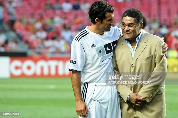 Portuguese former football player Figo embraces the football legend and former Benfica player Eusebio at the beginning of the Luis Figo Foundation...