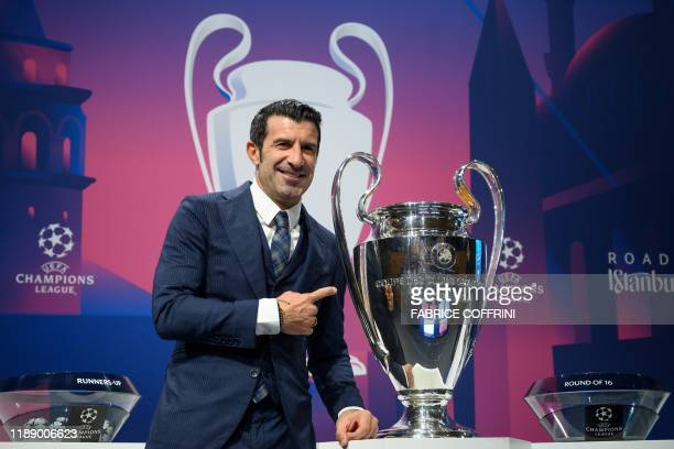 TOPSHOT Portuguese former player Luis Figo poses with the UEFA Champions League trophy prior to the UEFA Champions League football cup round of 16...