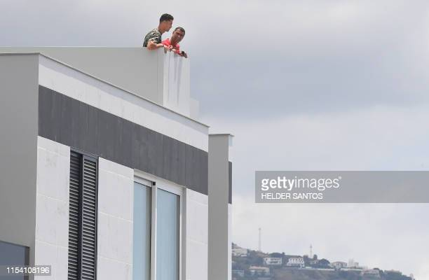 Portuguese forward Cristiano Ronaldo and his brother Hugo Aveiro look on from the balcony of an apartment building in Funchal on July 6, 2019. -...