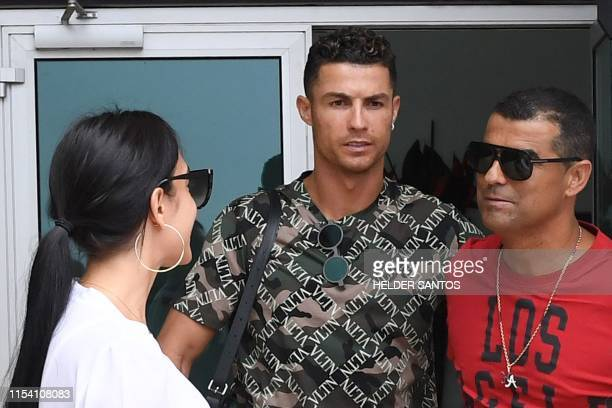 Portuguese forward Cristiano Ronaldo and his Spanish girlfriend Georgina Rodriguez are welcomed by his brother Hugo Aveiro upon their arrival in...
