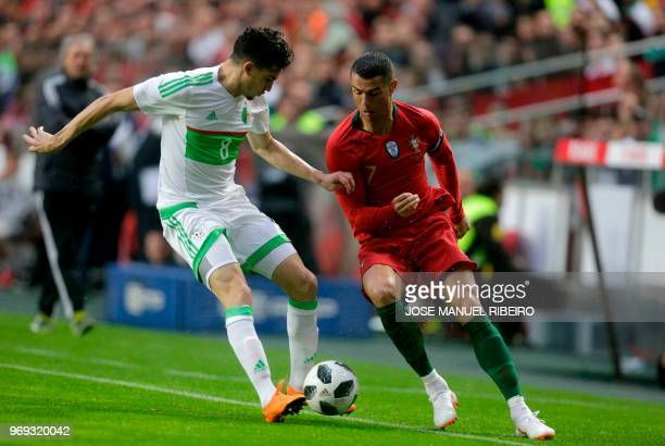 Portuguese forward Cristiano Ronaldo vies with Algerian midfielder Zinedine Ferhat during the friendly football match between Portugal and Algeria on...