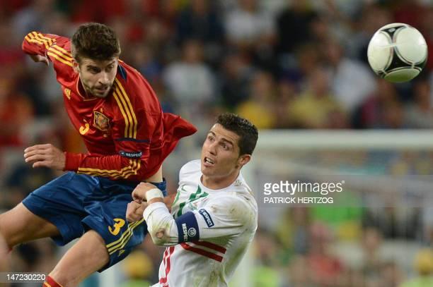Portuguese forward Cristiano Ronaldo vies with Spanish defender Gerard Pique during the Euro 2012 football championships semi-final match Portugal vs...