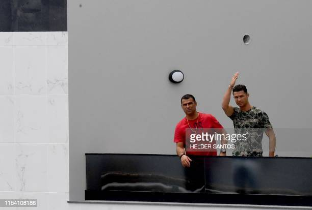 Portuguese forward Cristiano Ronaldo waves next to his brother Hugo Aveiro from the balcony of an apartment building in Funchal on July 6, 2019. -...