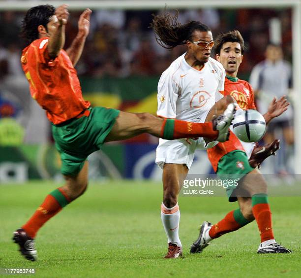 Portuguese forward Luis Figo kicks the ball next to Dutch midfielder Edgar Davids and Portuguese midfielder Deco 30 June 2004 at the Alvalade stadium...