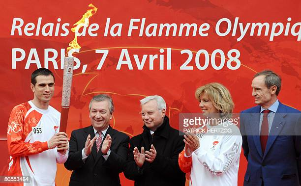 Portuguese forward of Paris SaintGermain football club Pauleta holds the Beijing olympic torch next to Paris mayor's deputy for Sports Jean...
