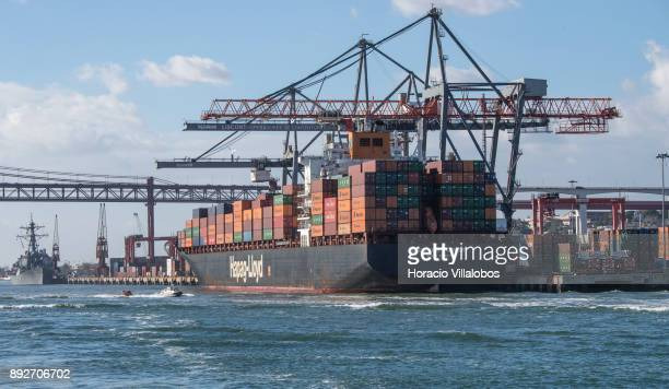 Portuguese Maritime Police fast boat sails near HapagLloyd Singapore Express Container Ship moored and downloading containers at Liscont containers...