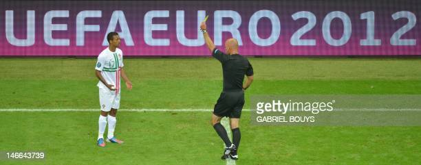 Portuguese midfielder Nani is given a yellow card by English referee Howard Webb during the Euro 2012 football championships quarterfinal match...
