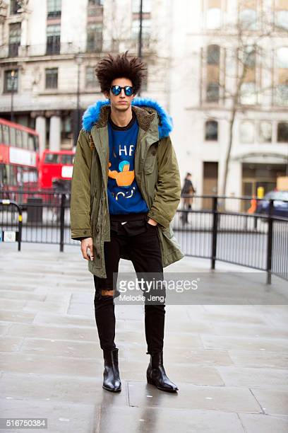 Portuguese model Luis Borges wears a green Diesel parka with a blue fur lining an Andrea Crews graphic blue shirt Illesteva blue reflective...