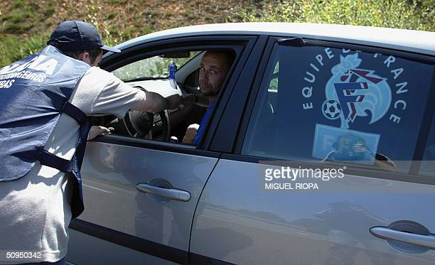 Portuguese national policeman inspects a French car at the frontier between Portugal and Spain in Valenca do Minho northern Portugal 11 June 2004...
