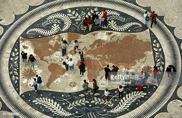 Portuguese pedestrians walk over a world map on the pavement beneath the Monument of Discoveries Lisbon The world's landmass is represented here in a...