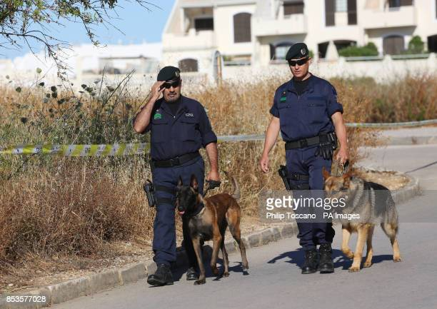 Portuguese police officers walk with dogs near a cordoned off area of scrubland close to where Madeleine McCann went missing seven years ago in the...