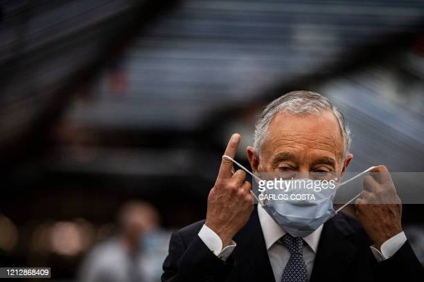 Portuguese President Marcelo Rebelo de Sousa adjusts his face mask during a visit to the Volkswagen Autoeuropa car factory in Palmela, 30 kms south...