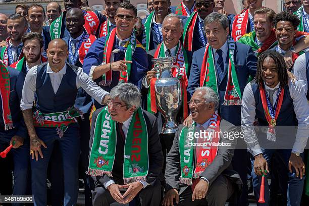 Portuguese President Marcelo Rebelo de Sousa holds the Euro 2016 trophy surrounded by the National Soccer Team and flanked by Cristiano Ronaldo , the...