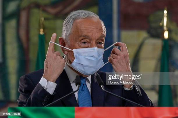 Portuguese President Marcelo Rebelo de Sousa takes off his protective mask before delivering remarks on electoral evening in the University of Lisbon...