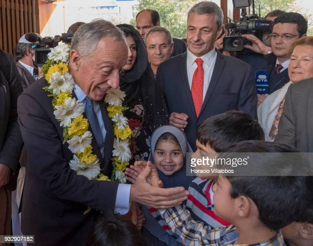 Portuguese President Marcelo Rebelo de Sousa wears a garland of flowers while being greeted by community children in the city's Central Mosque upon...