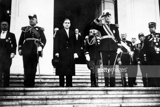 Portuguese President Oscar Carmona and Portuguese Prime Minister Antonio de Oliveira Salazar listen to national anthem during the reopening of the...