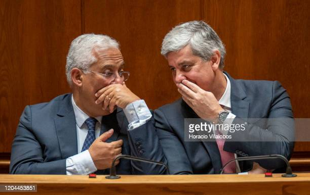 Portuguese Prime Minister Antonio Costa Finance Minister Mario Centeno cover their mouths while talking during the debate in the Assembleia da...