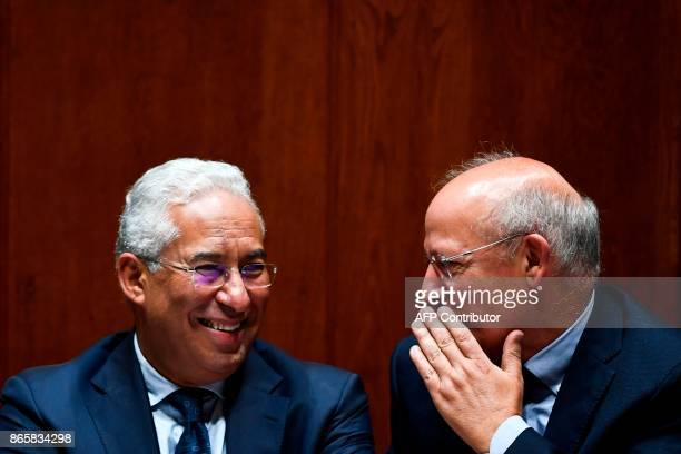 Portuguese Prime Minister Antonio Costa smiles as he listens to Foreign Minister Augusto Santos Silva during the debate of a censure motion tabled by...