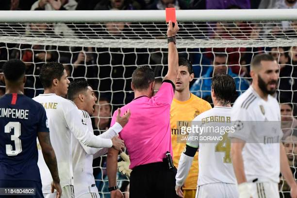 Portuguese referee Artur Dias hands a red card to Real Madrid's Belgian goalkeeper Thibaut Courtois during the UEFA Champions League group A football...