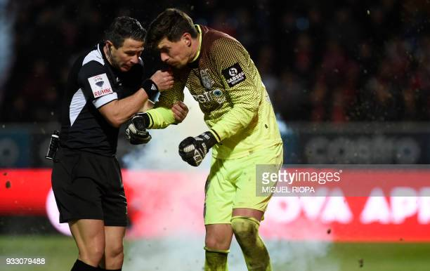 Portuguese referee Manuel Mota helps Feirense's Brazilian goalkeeper Caio Secco as a firecracker explodes next to him during the Portuguese League...