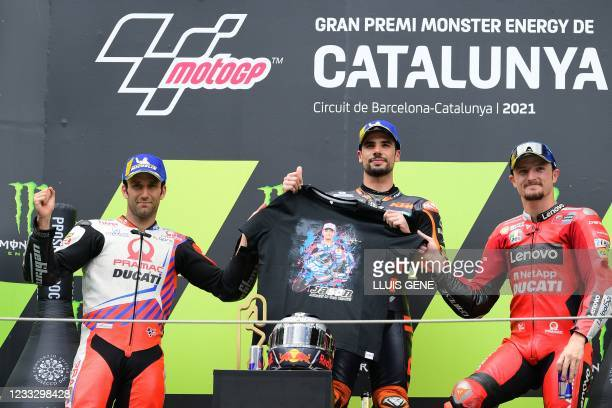 Portuguese rider Miguel Oliveira celebrates on the podium with Ducati-Pramac French rider Johann Zarco and Ducati Australian rider Jack Miller after...