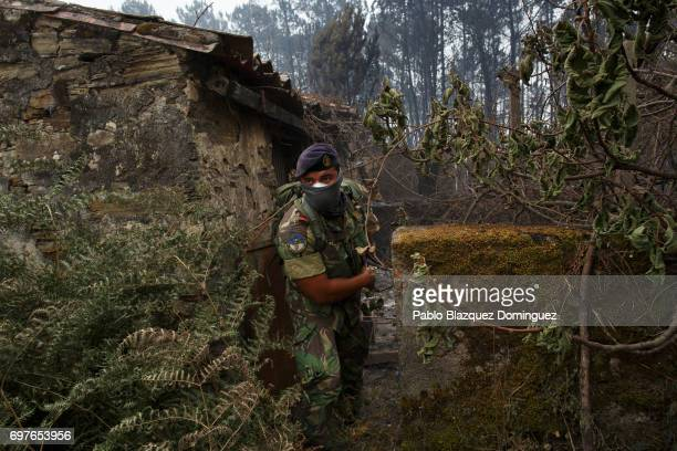 Portuguese soldier checks the area and empty properties for possible human remains after a wildfire took dozens of lives on June 19 2017 near...